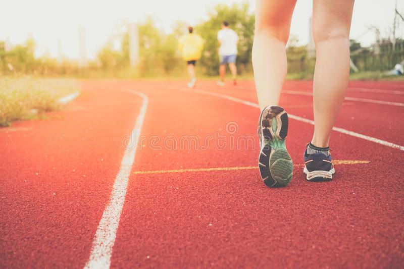Woman wear sport shoe on to run in running court background. stock images