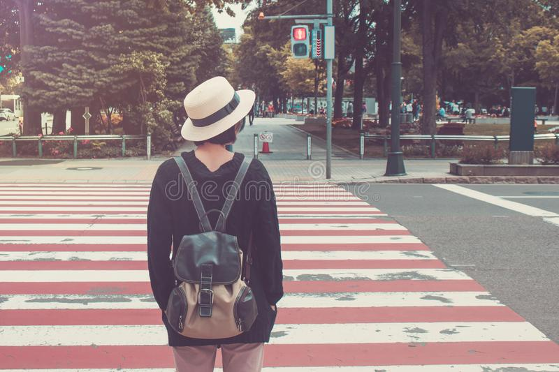 Woman wear white weave hat and black overcoat. She standing on footpath and waiting for crossing the road. royalty free stock photography