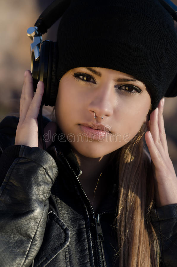 Woman wearing beanie hat with headphones. Beautiful girl wearing beanie hat with headphones listening to music stock photos