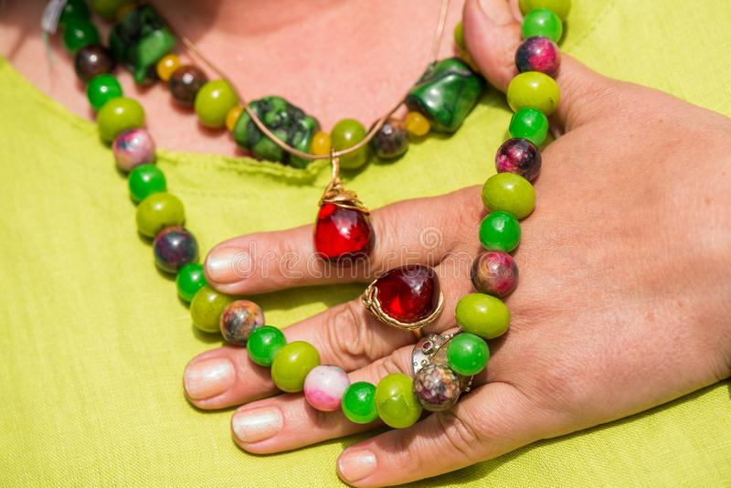 Woman wearing beautiful gemstone necklace and golden ring with amber. stock photography