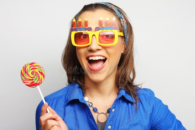 Woman wearing big sunglasses holding lollipop. Funny woman wearing big bright sunglasses holding lollipop royalty free stock image