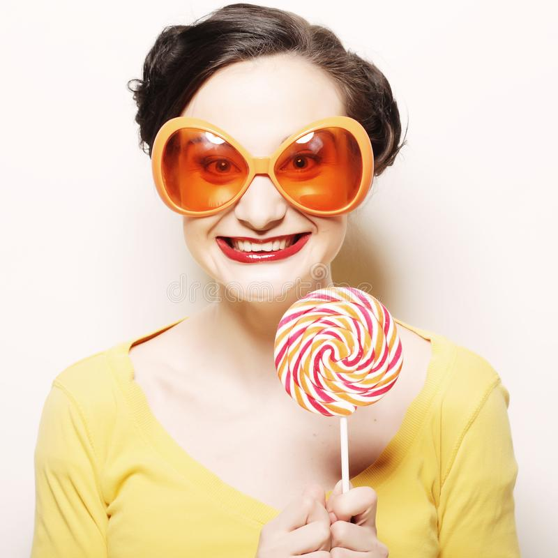 Woman wearing big sunglasses holding lollipop. Funny woman wearing big bright sunglasses holding lollipop stock photos