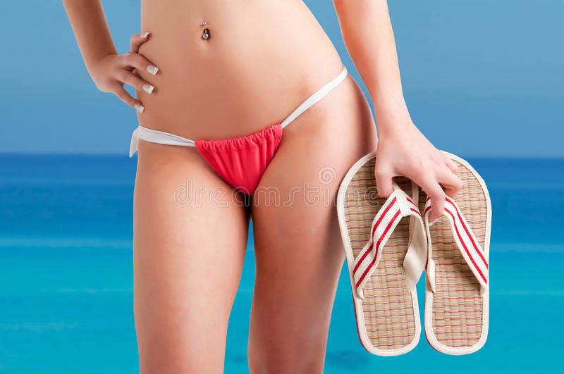 Woman in Bikini. Woman wearing a bikini and holding flip-flops, with the ocean behind royalty free stock photo