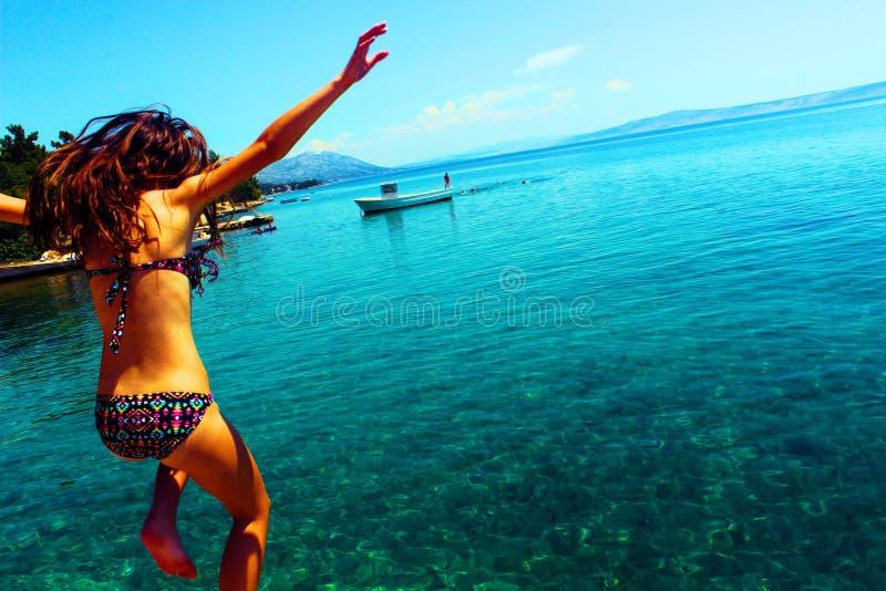 Woman Wearing Bikini Jumping to the Beach royalty free stock photography