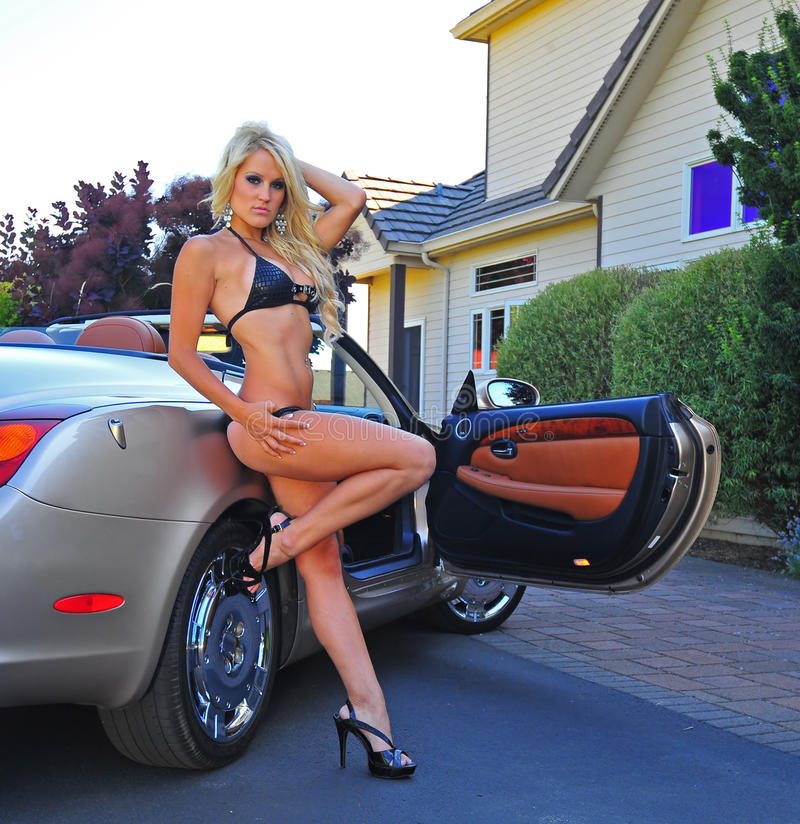 Woman wearing bikini leaning against sports car stock photo