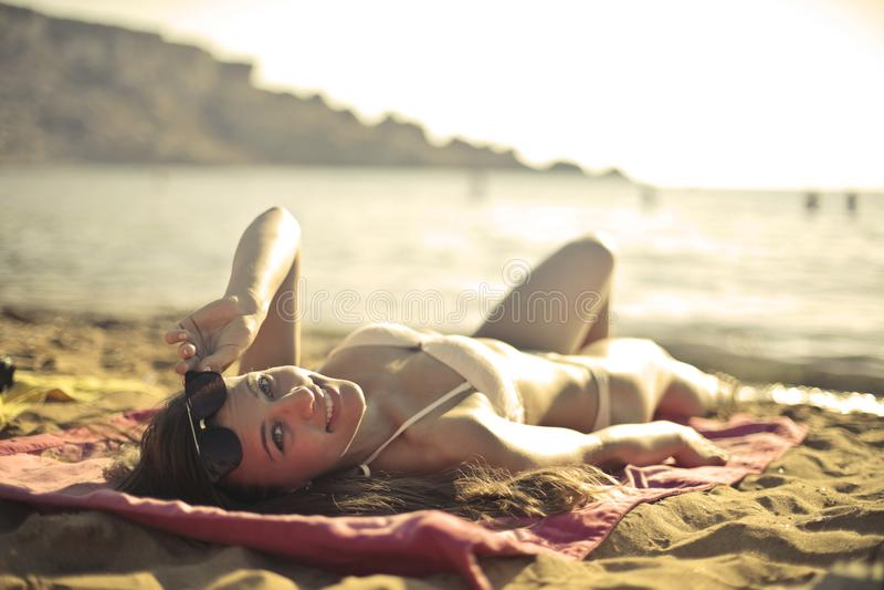 Woman Wearing Bikini Lying on Red Mat Near Seashore at Daytime royalty free stock photography