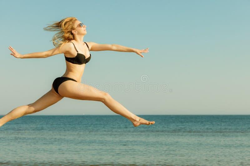 Woman wearing bikini playing, jumping near sea stock images