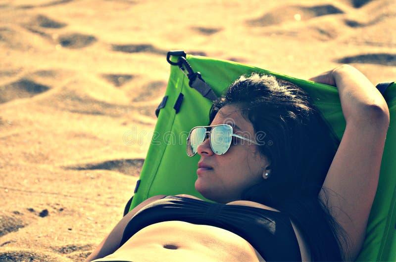 Woman Wearing Bikini Top Lying on Bed Beside Sand at Daytime royalty free stock image