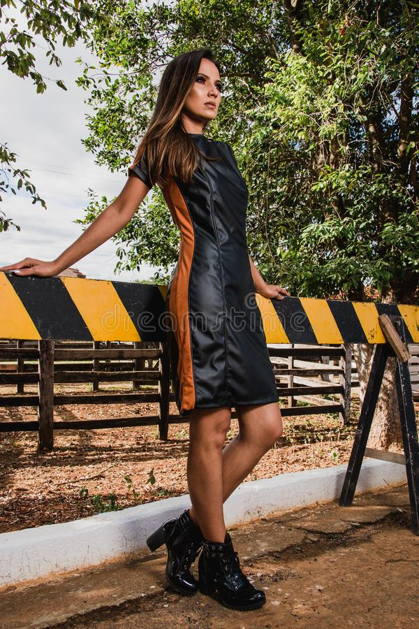 Woman Wearing Black and Brown Leather Midi Dress and Black Chunky Heeled Boots royalty free stock photo