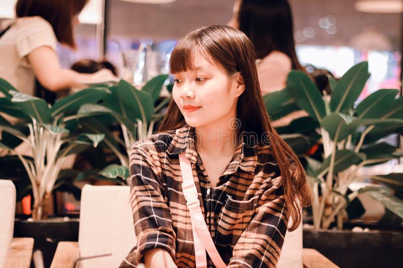 Woman Wearing Black and Brown Plaid Sport Shirt Sitting on Sofa stock photo