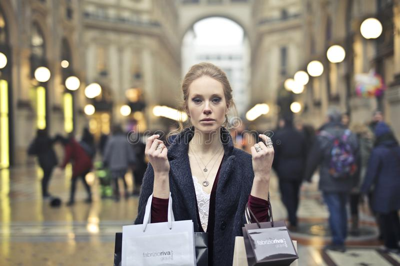 Woman Wearing Black Coat Holding Assorted-color Shopping Bags on Building stock images
