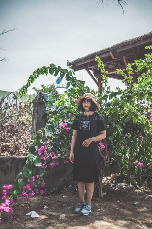 Woman Wearing Black Crew-neck Dress Standing Beside Pink Flowers royalty free stock image
