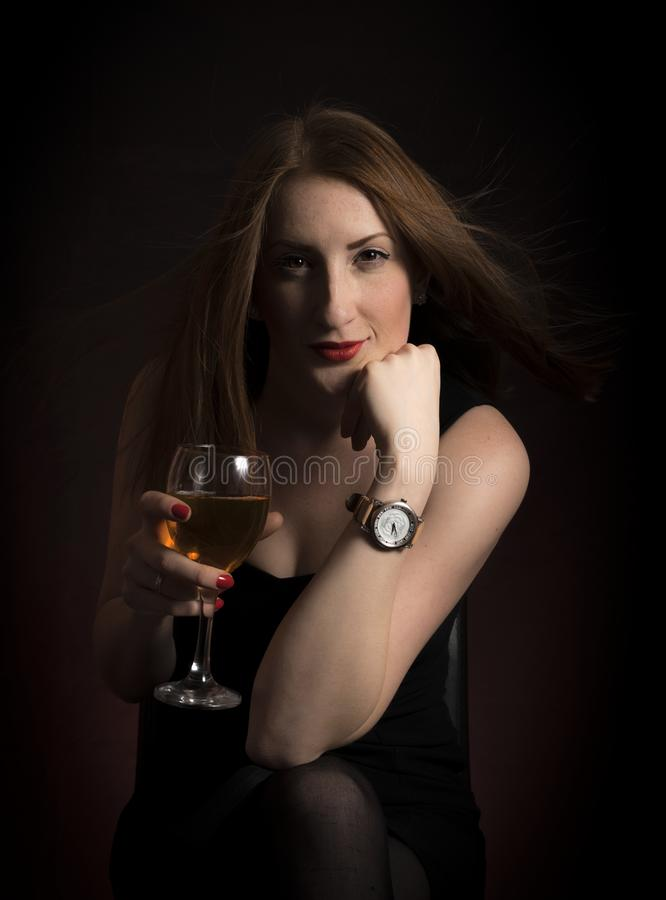 Woman Wearing Black Dress Holding Clear Wine Glass in Dark Room stock photography