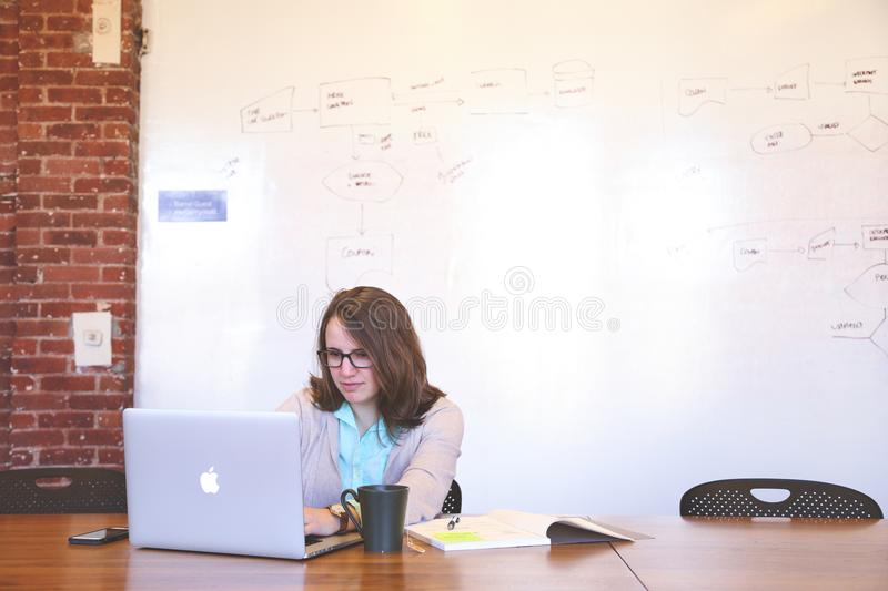Woman Wearing Black Framed Eyeglasses and Teal Button-up Shirt and Beige Blazer Sitting at Table Near White Macbook royalty free stock photos