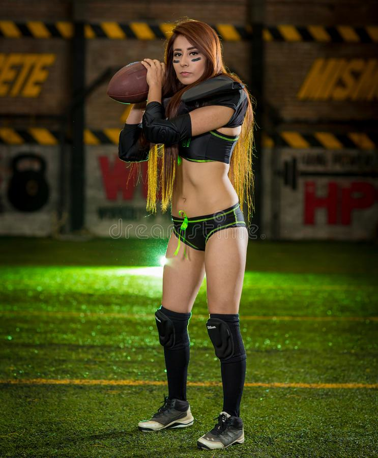 Woman Wearing Black-and-green Sports Bra and Pantie Holding Rugby Ball royalty free stock images