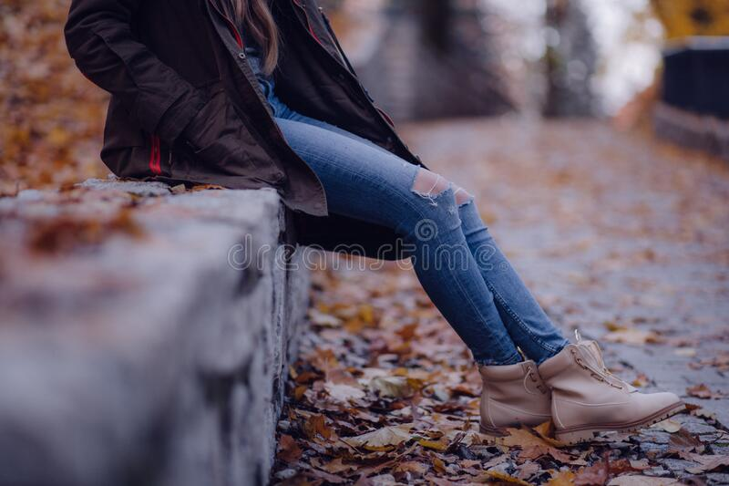 Woman Wearing Black Jacket Blue Distressed Jeans And Brown Boots Sitting On Gray Concrete Barrier Free Public Domain Cc0 Image