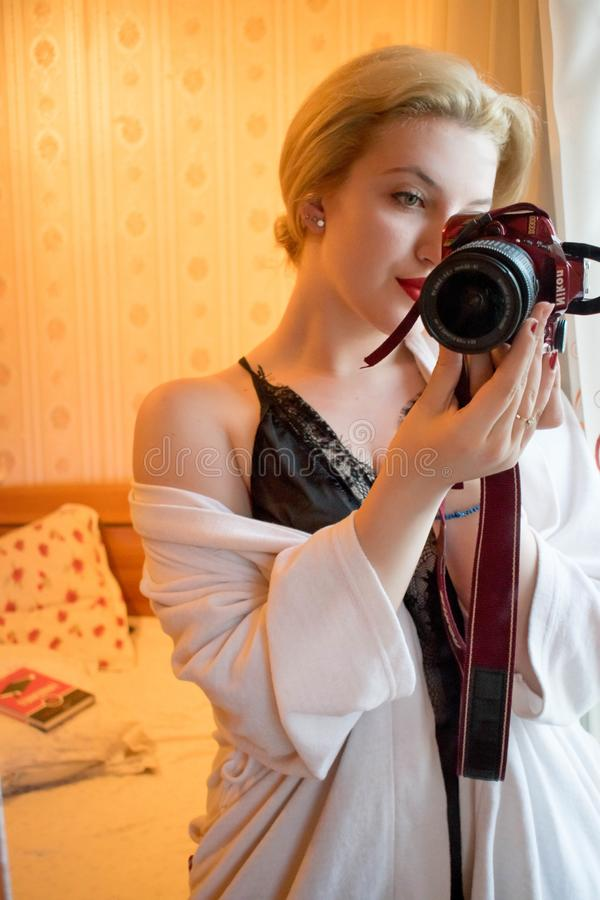 Woman Wearing Black Lace Floral Spaghetti Strap Dress Holding Black and Red Samsung Bridge Camera in Room stock images