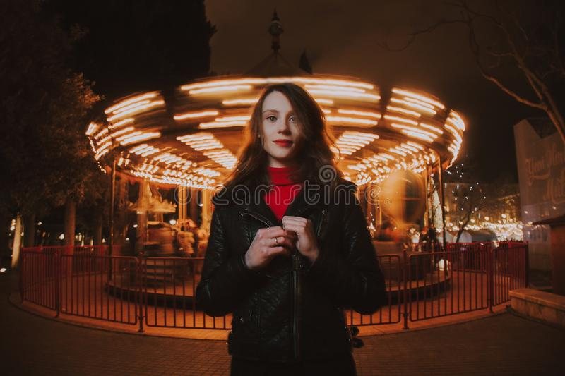 Woman Wearing Black Leather Jacket and Red Turtle-neck Shirt Standing in Front of Carousel Ride stock photography