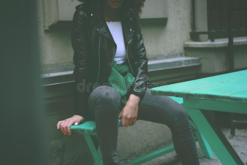 Woman Wearing Black Leather Jacket Sitting on Green Wooden Bench royalty free stock photography