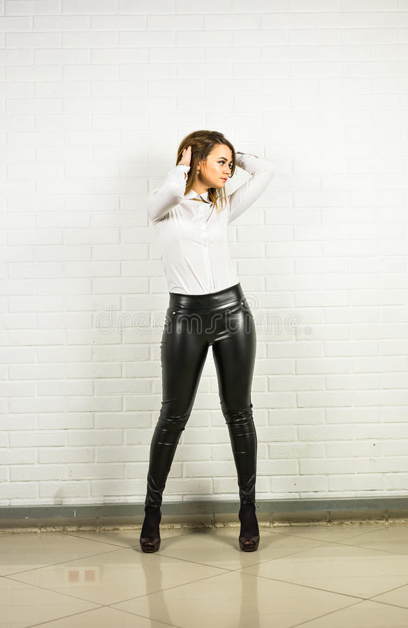 2aee10272 Woman wearing black leather pants indoors. Woman wearing black leather pants  and high heel shoes