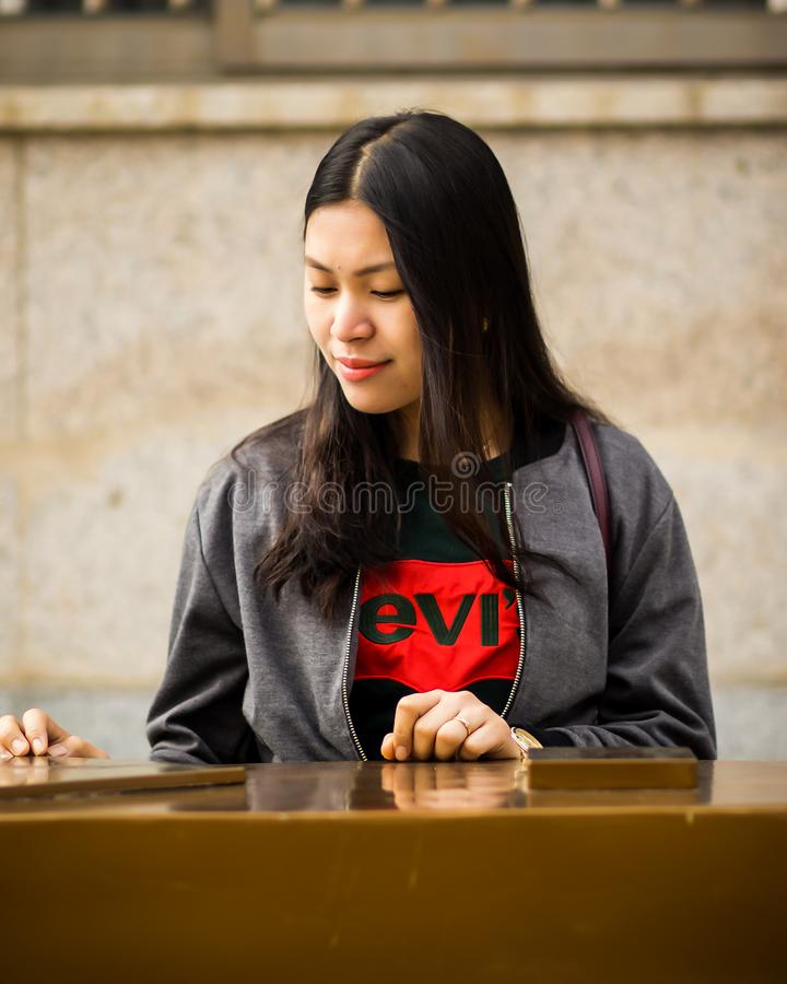 Woman Wearing Black Levis Crew-neck Shirt and Gray Zip-up Jacket royalty free stock image