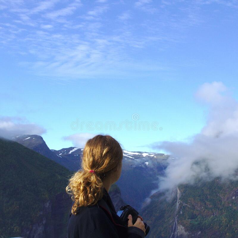 Woman Wearing Black Long Sleeve Shirt Watching on Green and Brown Mountain Under White and Blue Sky during Daytime stock images