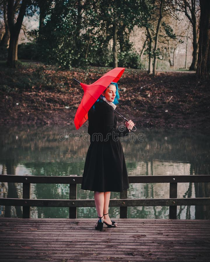 Woman Wearing Black Long-sleeved Dress Holding Red Umbrella stock photo