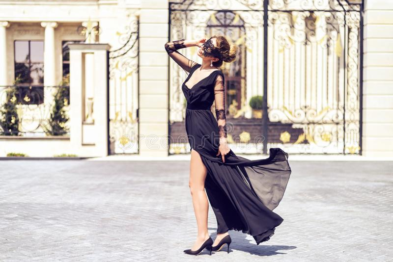 Woman wearing a black mask and black dress outdoor portrait. Classic vintage looks. Woman wearing a black mask and black dress outdoor portrait. Classic vintage stock image