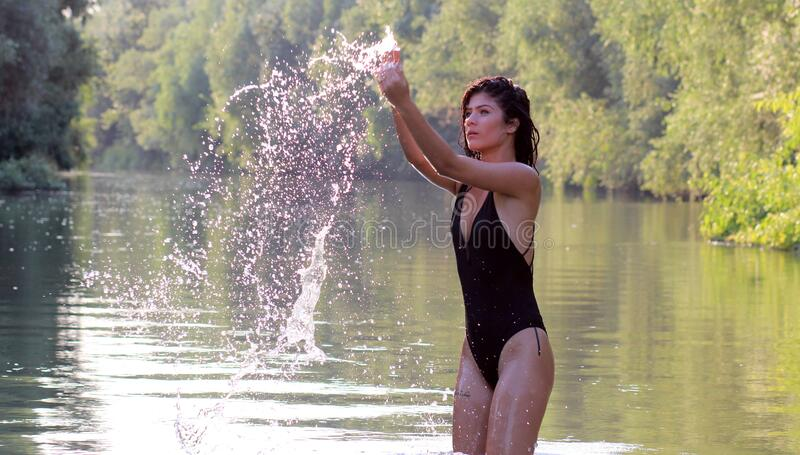 Woman Wearing Black Monokini Playing With Water royalty free stock images