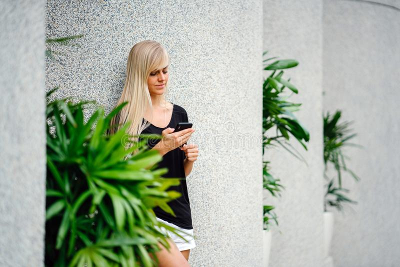 Woman Wearing Black Scoop-neck Shirt Standing in Front on Concrete Column Holding Smartphone stock images