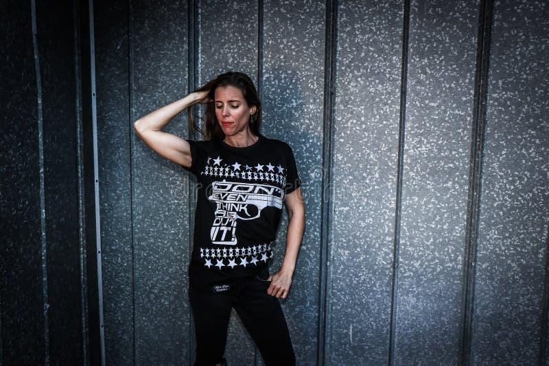 Woman Wearing Black Shirt and Pants Near Gray Wall royalty free stock image