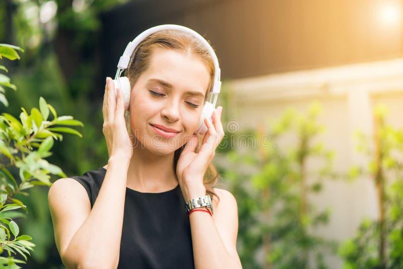 Woman Wearing Black Sleeveless Dress Holding White Headphone at Daytime stock photos