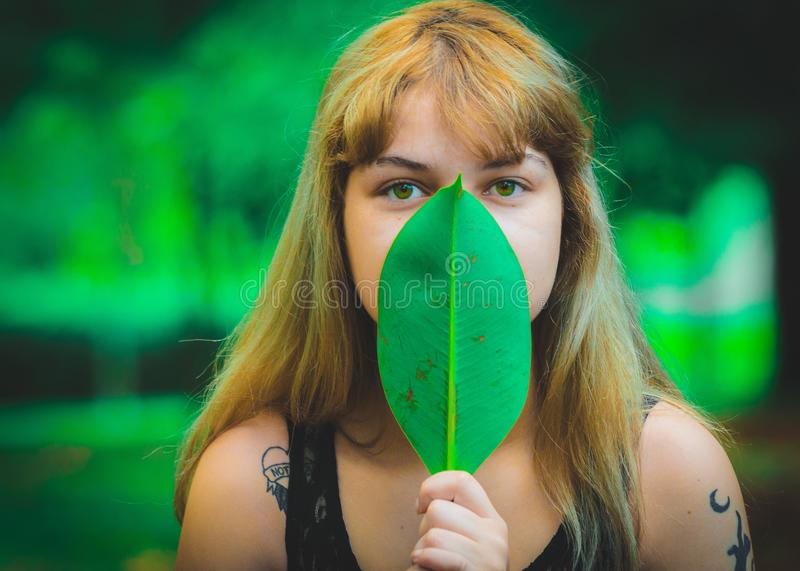 Woman Wearing Black Sleeveless Top Covering Mouth Using Green Leaf stock images
