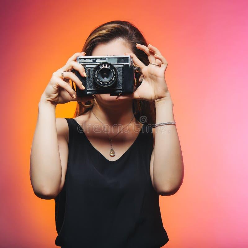 Woman Wearing Black Sleeveless Top Holding Gray Camera stock image