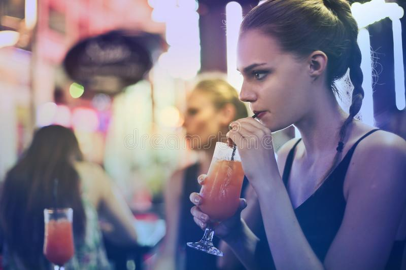 Woman Wearing Black Spaghetti Strap Top and Sipping Drink royalty free stock images