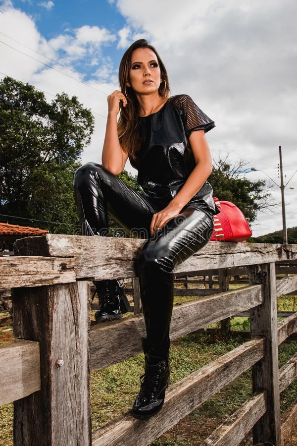Woman Wearing Black Suit on Farm Sitting on Fence royalty free stock photography