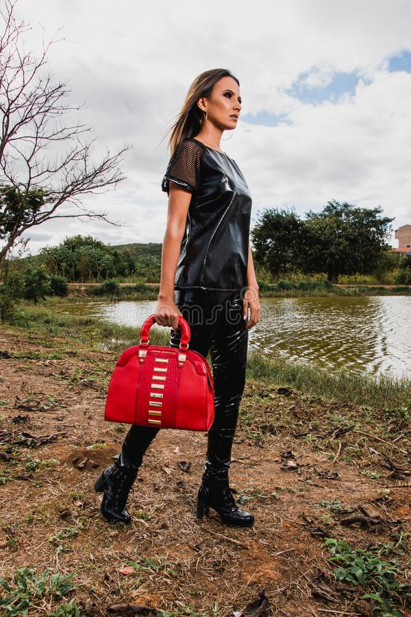 Woman Wearing Black Suit Holding Red Leather Duffel Bag during Day stock images