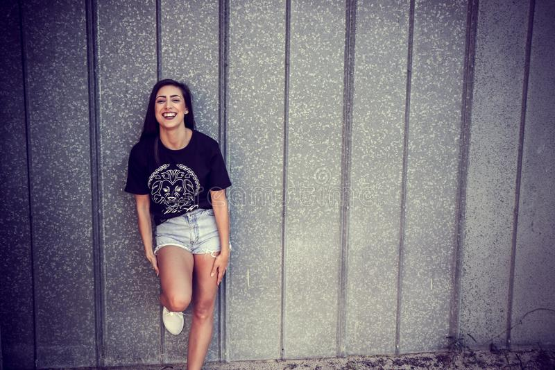 51d34b1014c178 Public Domain Image Woman Wearing Black And White Crew-neck T-shirt And  Gray Denim Short Shorts Outfit Leaning On Gray Wall
