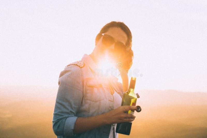 Woman Wearing Blue Denim Jacket Holding Wine Bottle in Golden Hour Photo stock image