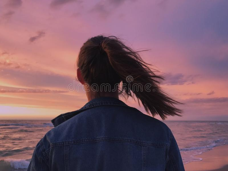 Woman Wearing Blue Denim Jacket Looking At The Beach stock image