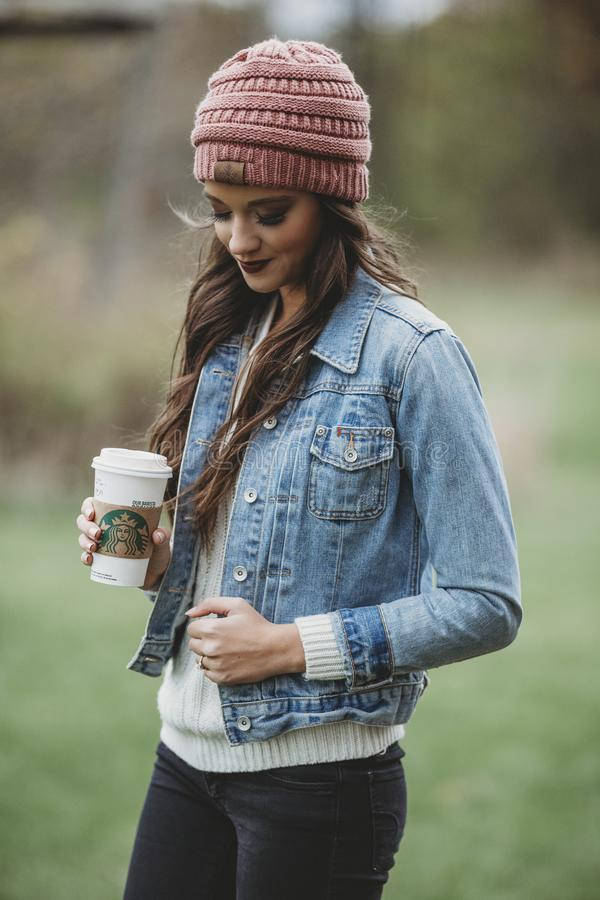 Woman Wearing Blue Denim Jacket and Pink Knit Cap Holding Starbucks Coffee stock photos