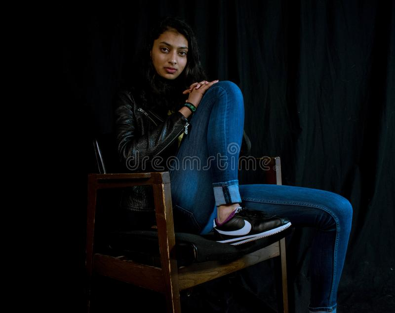 Woman Wearing Blue Jeans Sitting on Brown Wooden Armchair stock photo