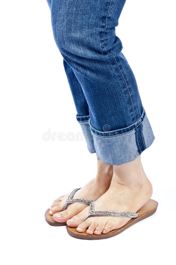 Woman Wearing Blue Jeans and Stylish Flip Flops. Woman wearing capri blue jeans and a pair of stylish flip flops isolated on white stock image