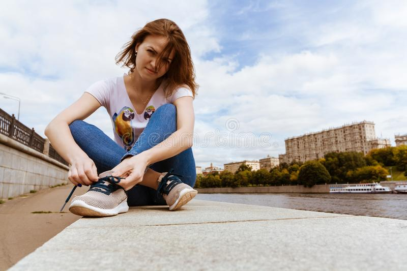 portrait of pretty girl in blue jeans tying shoelaces on the old embankment stock photo