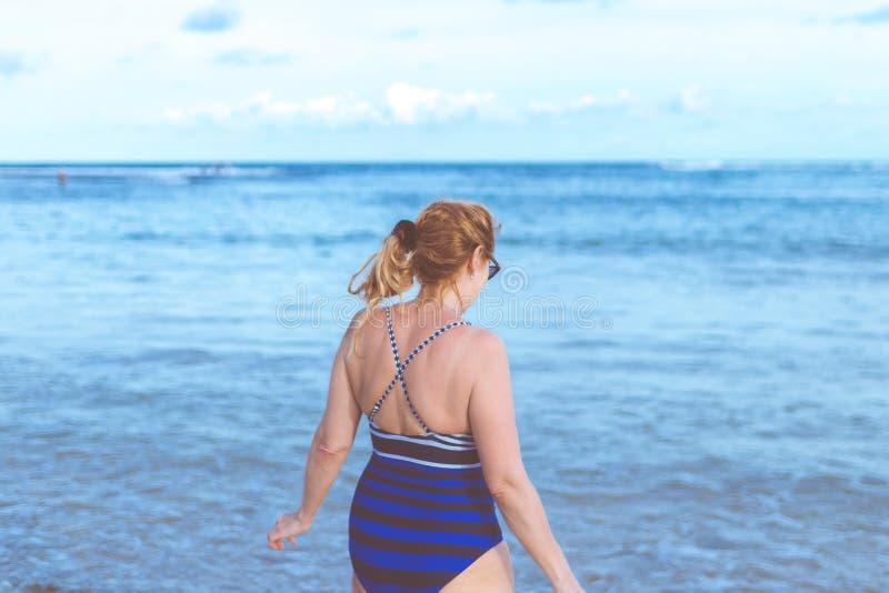 Woman Wearing Blue Monokini Standing Beside Body Of Water Under Blue Sky stock photo