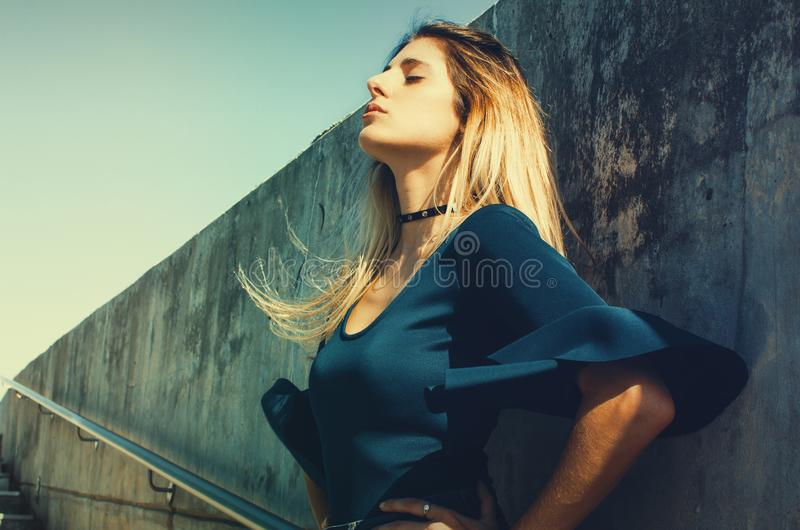 Woman Wearing Blue Scoop-neck Top Standing Near Gray Concrete Wall royalty free stock photography