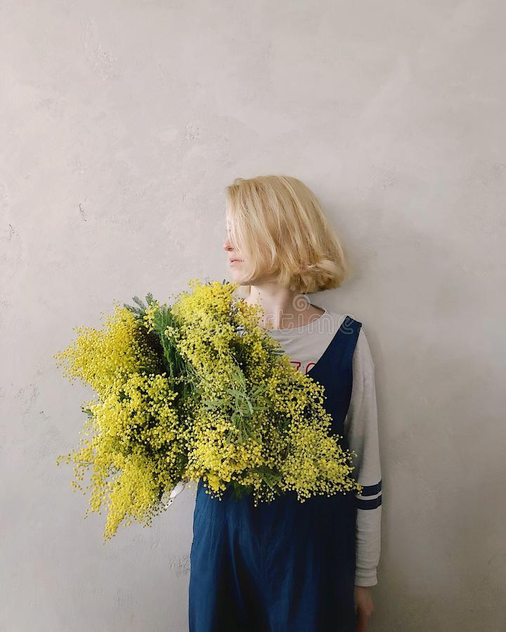Woman Wearing Blue V-neck Sleeveless Top While Holding Yellow Petaled Flower stock photos