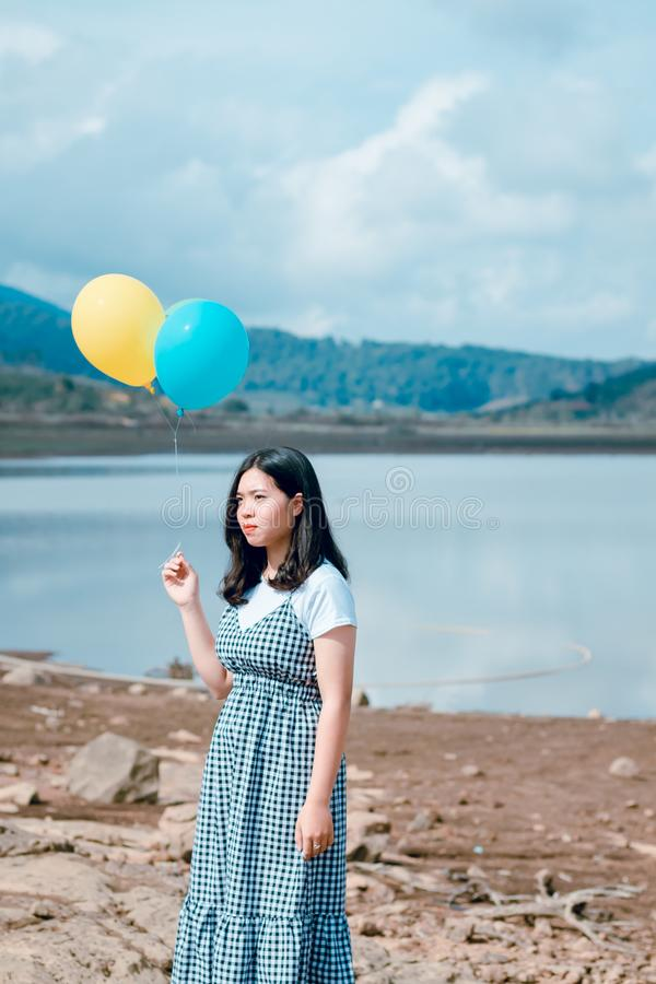 Woman Wearing Blue and White Plaid Dress Holding Blue and Yellow Balloons Near Calm Body of Water at Daytime stock image