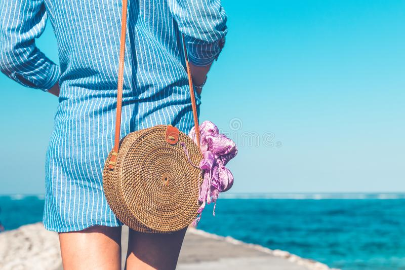 Woman Wearing Blue and White Striped Dress With Brown Rattan Crossbody Bag Near Ocean royalty free stock images