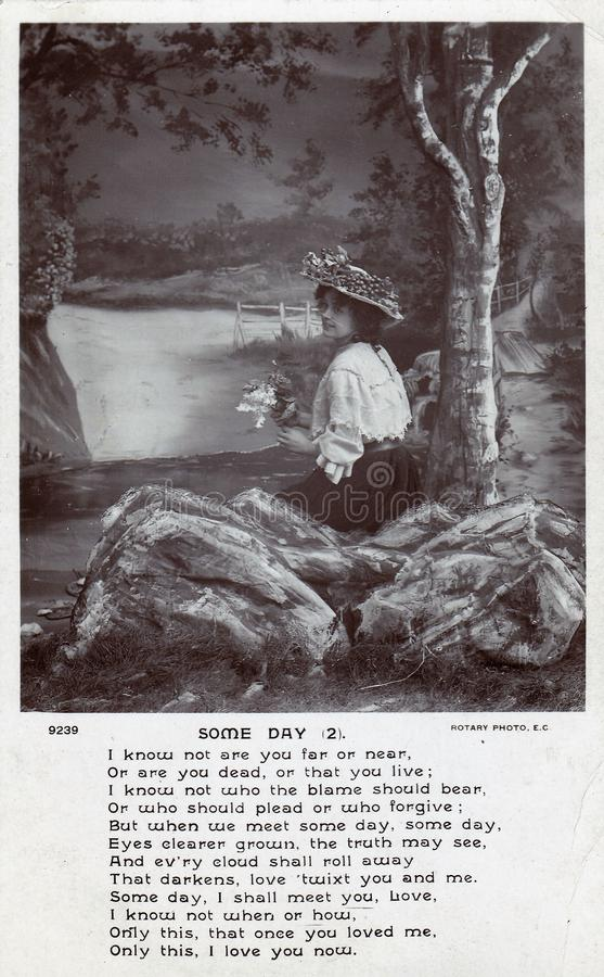 Vintage black and white postcard with `Some Day` poem showing lady with flowers and wearing bonnet. Woman wearing a bonnet and holding flowers on a vintage black royalty free stock image